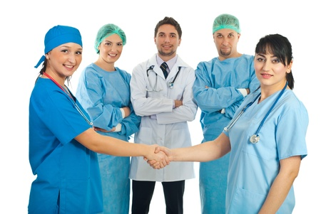 Hospital doctors women give handshake and their team of different doctors smiling in background photo