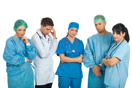 Sad doctors team with problems standing in a row and thinking at solutions isolated on white background photo