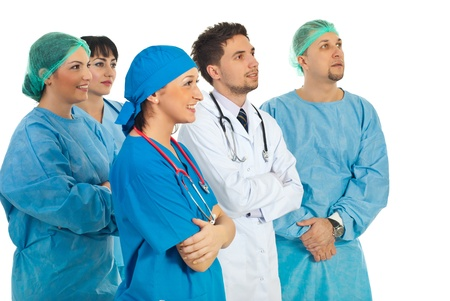 Doctors team standing in a group and looking away to copy space isolated on white background photo