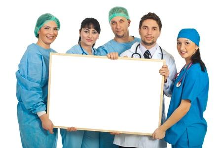 Alegre equipo de cinco médicos sosteniendo una bandera en blanco aislada en fondo blanco