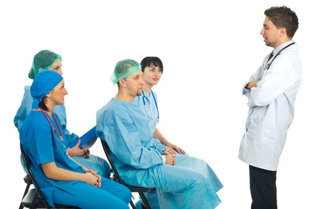 Young doctor man having a speech at conference and other four different doctors listening him isolated on white background photo