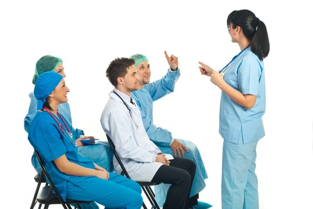 health questions: Doctor woman pointing to a surgeon man with hand raised who know the answer to question at conference