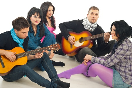 Friends enjoying time together,guys playing acoustic guitars and the girls listening them and all sitting on floor photo