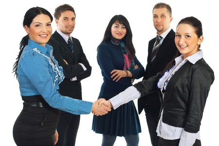 Attractive two business women gives handshake in front of their teamwork isolated on white background photo