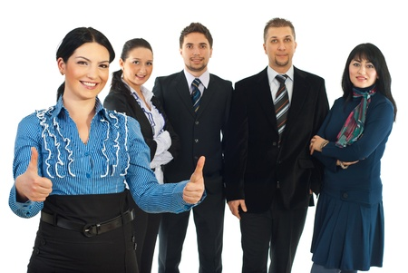 Beautiful business woman giving thumbs up with both hands and smiling in front of camera and her partners  standing in background isolated on white background photo