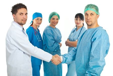 Two doctors men giving handshake in front of three doctors women team isolated on white background photo