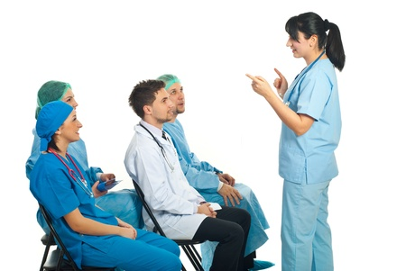 Physician woman giving explanations to her colleagues doctors sitting on chairs at seminar photo