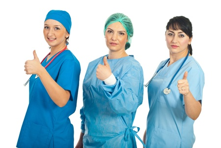 Three doctors women standing in a row and giving thumbs up isolated on white background photo