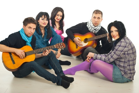 Five friends having a meeting and sitting on wooden  floor playing guitars and singing together  in a house Stock Photo - 8692179
