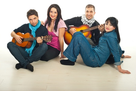 Two couples of young and mid adults sitting on wooden floor and playing acoustic guitars in a home photo