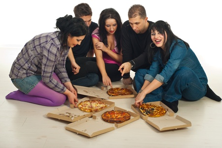 Five friends meeting and sitting on wooden floor in a home and sharing pizza together Stock Photo