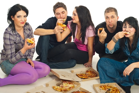 Five friends sitting on  wooden floor and eating pizza