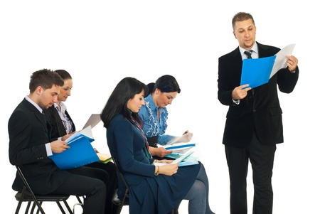 presentation folder: Business man reading from a folder at seminar and his colleagues business people checking their folders over white background