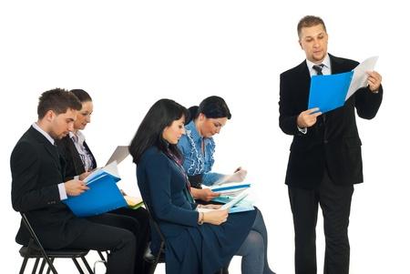 carpetas: Hombre de negocios leer desde una carpeta en el seminario y su gente de negocios de colegas comprobando sus carpetas sobre fondo blanco