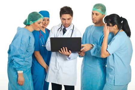 Group of five doctors having conversation and using a laptop isolated on white background photo