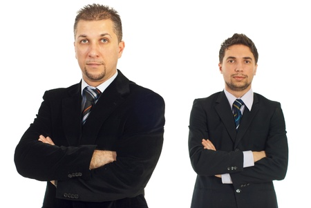 mains crois�es: Mid adult business man in front of camera standing with hands crossed and his young colleague in background