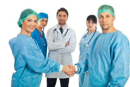 Two surgeons  giving handshake and their team smiling in background photo
