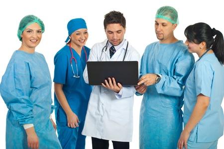 doctores: M�dicos amigables utilizando un ordenador port�til y una mujer de cirujano sonrientes mirando la c�mara aislado en fondo blanco Foto de archivo