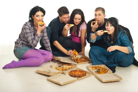 Group of five friends eating delivery pizza and sitting together on wooden floor photo