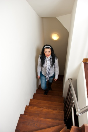 Woman climb up interior wooden  stairs in her home photo