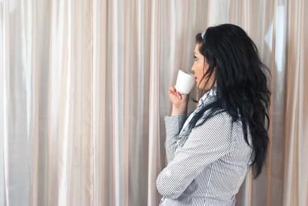 donna che beve il caff�: Donna pensiero bere caff� o t� e permanente nei pressi della finestra e guardando fuori attraverso tende Archivio Fotografico