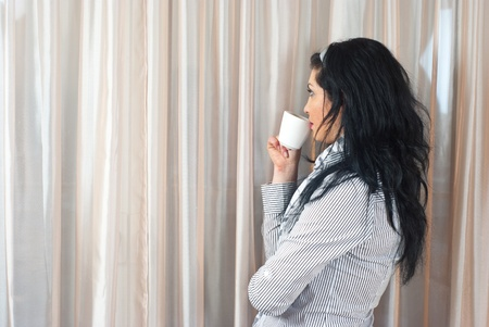 Thinking woman drinking coffee or tea and standing near window and looking outside through curtains photo