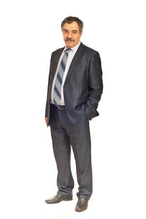 1 senior: Longitud total de hombre de negocios maduro permanente con la mano en el bolsillo traje aislada sobre fondo blanco