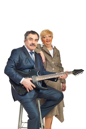 Mature business man in formal wear playing electronic guitar and being assisted by a woman isolated on white background photo