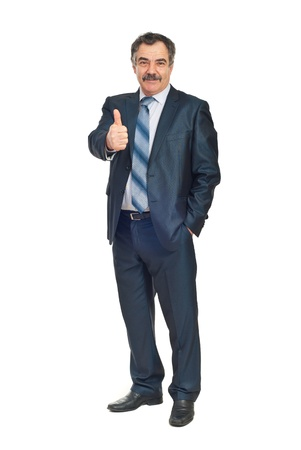 senior business: Full length of smiling senior business man giving thumb up and holding a hand into suit pocket isolated on white background