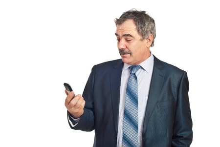Surprised mature business man holding a cellphone and reading isolated on white background photo