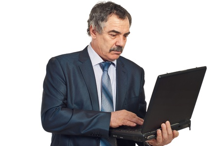 Serious middle aged executive man working on laptop isolated on white background photo