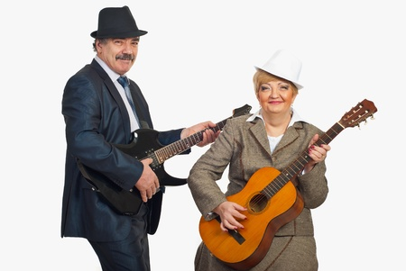 Middle aged couple wearing hats and elegant suits and playing guitars isolated on white backgroud photo