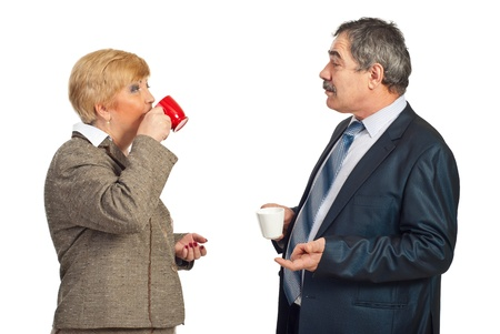 break in: Two mature business people drinking coffee in a business break and having conversation together isolated on white background