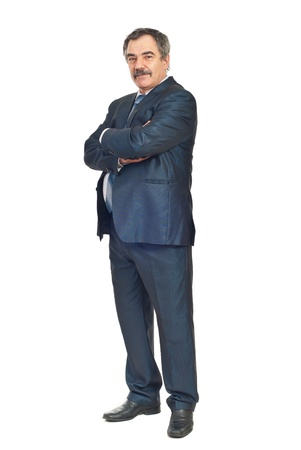 middle aged men: Full length of mature elegant business man standing with arms folded isolated on white background