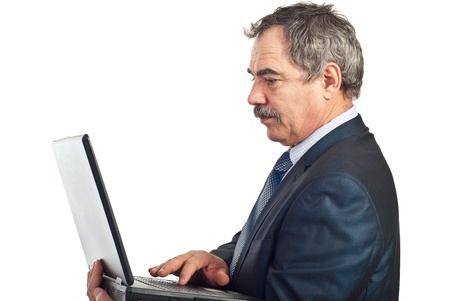 Profile of mature serious business man typying on laptop isolated on white background photo