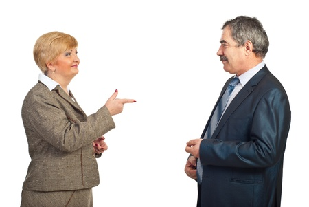 accuser: Mature business woman pointing to his colleague man and smiling isolated on white background