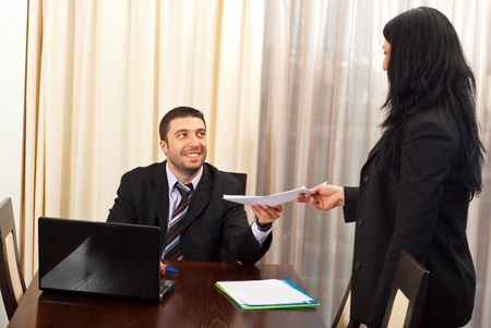 Happy business man giving some papers to a secretary woman  in a meeting room photo