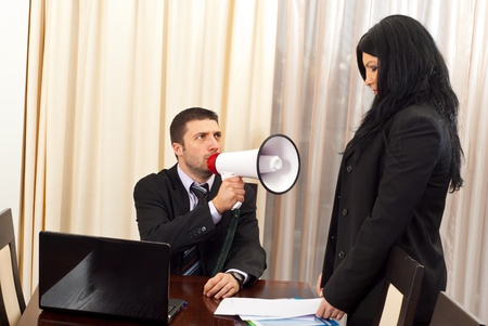 affraid: Furious manager man shouting in megaphone to an employee woman:You are fired! Stock Photo