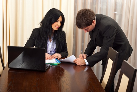 Business  man signing a contract for a manager woman  in a meeting room photo