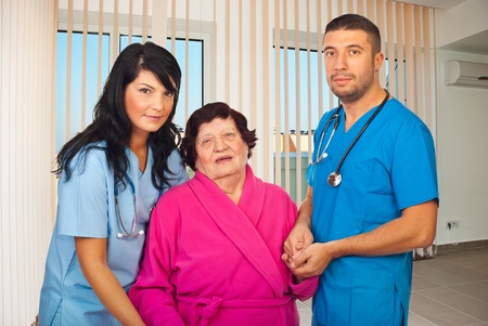 mid adults: Two mid adults doctors holding elderly woman hands to help her to walk in a hospital room