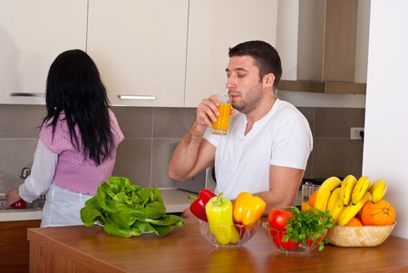 Mid adult couple in their kitchen wife washing vegetables and husband drinking orange juice photo
