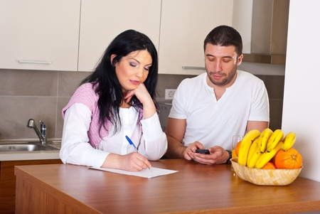 Sad couple calculate their bills and having conversation in kitchen Stock Photo - 8816252
