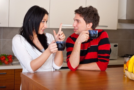 Young couple drinking coffee in the morning and having conversation in their kitchen photo