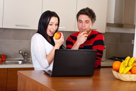 Young couple eating apples and using laptop in their kitchen  photo