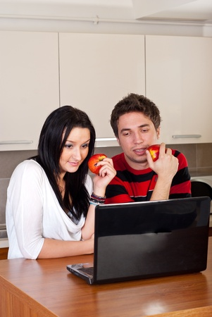 Young couple with apples having conversation and looking on laptop in their kitchen photo