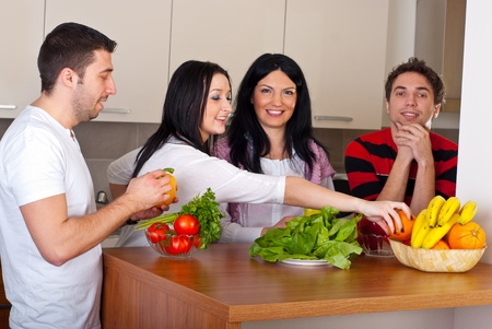 Happy group of friends  preparing food with fresh vegetables and having conversation in kitchen photo