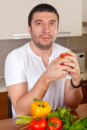 Serious mid adult man holding apple and looking at camera in his kitchen Stock Photo - 8816262