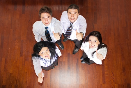 Top view of four business people giving thumbs and looking up