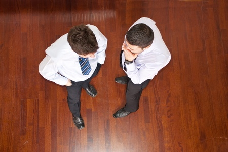 Top view of business man telling his collegue a secret and holding hands to month and the other man listening him Stock Photo - 8902710