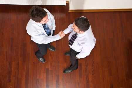 congratulate: Top view of two business men giving hand shake and congratulate each other